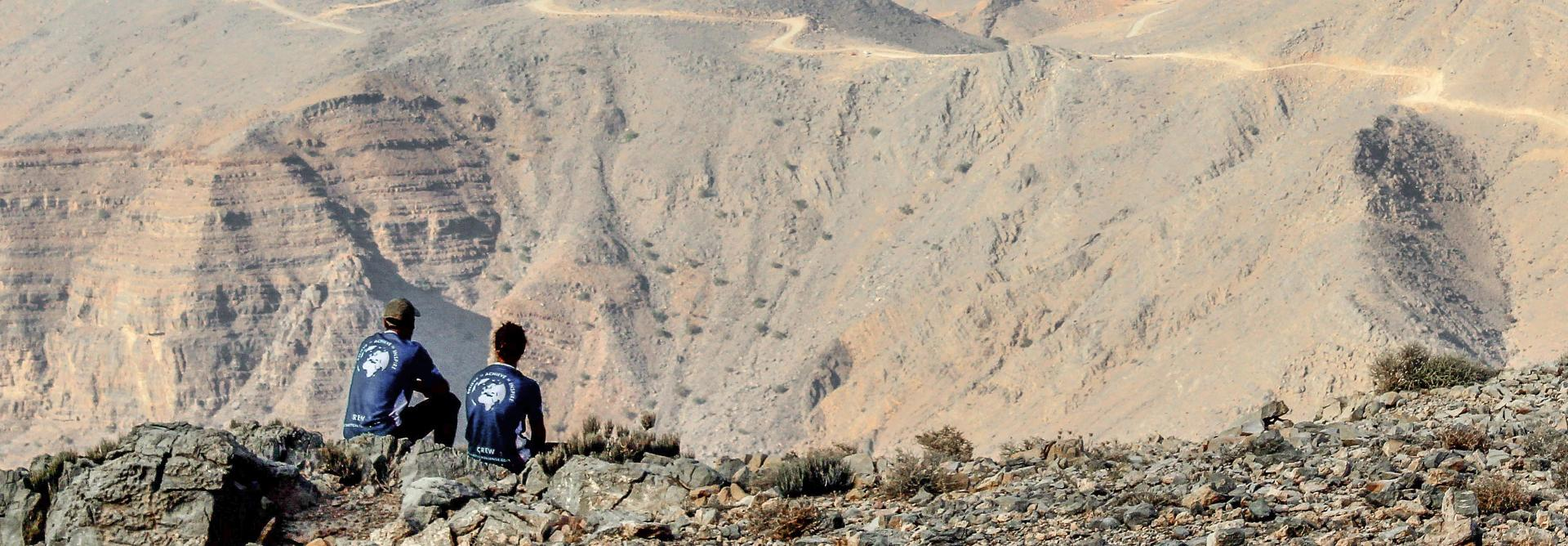 two hikers rest on the charity challenge Oman mountain trek